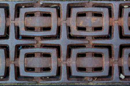 metal grate: A series of rectangles appear as buckles in a decorative metal grate along a the downtown thorough fair of a small city Stock Photo