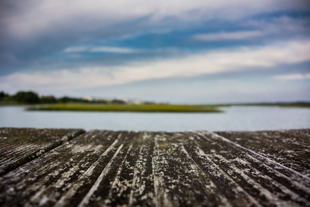 intercoastal: A sharp focus on a wooden boardwalk in front of a blurred marsh inlet