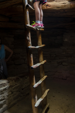 A child crawls down to explore a kiva in the ruins at a national monument Stock Photo