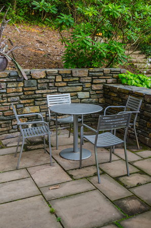 catch up: A table with four chairs in an outdoor cafe makes a cozy spot to catch up over lunch or coffee Stock Photo