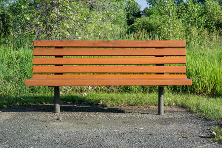 A wooden bench offers a place to sit in a suburban park