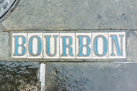 bourbon: A freshly rinsed sidewalk sign notes the corner of Bourbon Street in New Orleans