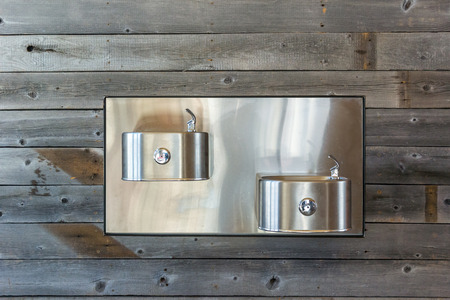 ski lodge: Modern stainless steel water fountains against a rustic wood wall