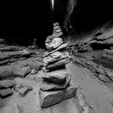 A cairn of small rocks in a slot canyon guides hikers