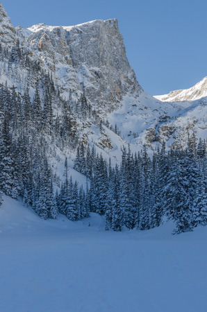dream lake: Snowy mountain over Dream Lake vertical with snow covered trees and lake surface