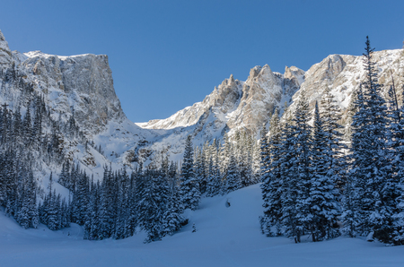 Snowy mountains loom over Dream Lake in the Rocky Mountains of Colorado