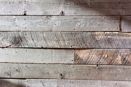 ski lodge: Rough wood wall wide shot captures light and shadow off an unsanded wooden wall
