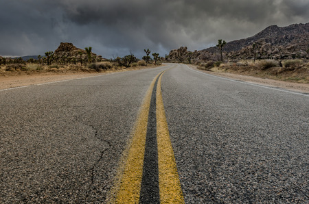 macadam: Low angle view of desert road just before a storm with focus on the yellow center stripe