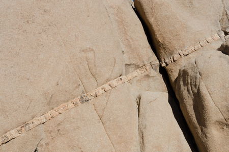 seam: Seam of Rock in sand close up background image