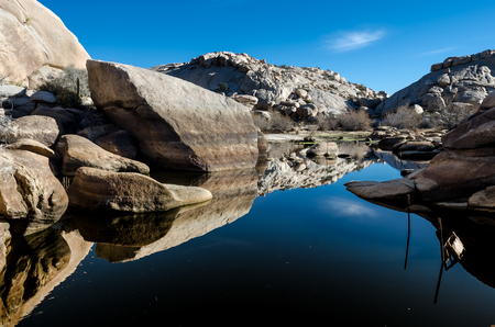 barker: Barker Dam reflecting boulders on a clear winter day Stock Photo