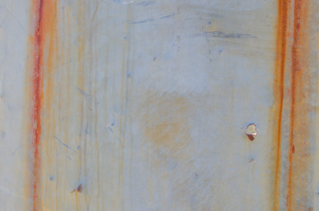 industrial park: Vertical streaks of rust and bullet hole on sheet metal at an old mill