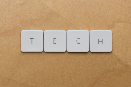 shorthand: Keyboard letters spell the shorthand word tech on a desk background