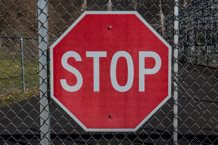 chainlink: Stop sign on chainlink gate at a water power plant Stock Photo