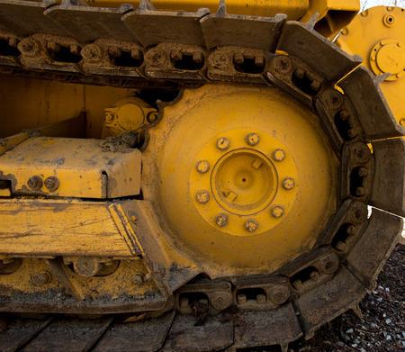 caked: Bull dozer tread with caked mud and dirt