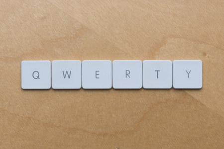 qwerty: Keyboard letters spell qwerty against a desk background