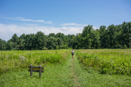 appalachian trail: Female hiker through open field in a park in Virginia along the Appalachian Trail Stock Photo