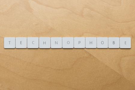 Keyboard letters spell technophobe against a desk background