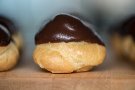 cream puff: Single cream puff on butcher block with a chocolate ganache topping