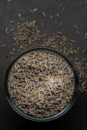 close p: Dried lavender in bowl will spill over onto slate cutting board Stock Photo
