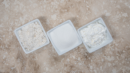 starch: Flour, Sugar, and Corn Starch in Bowls on a travertine background Stock Photo