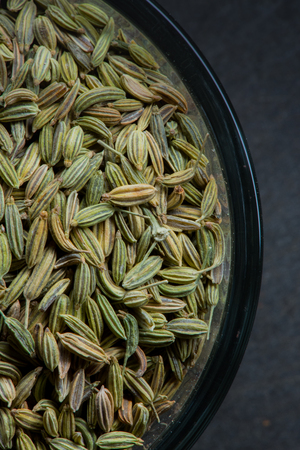 fennel seed: Cropped fennel seed bowl left of slate background