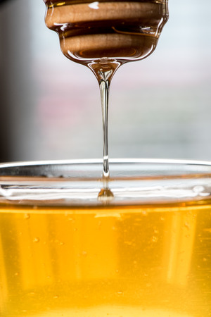 honey blonde: Honey drizzling from wooden dipper back into glass bowl