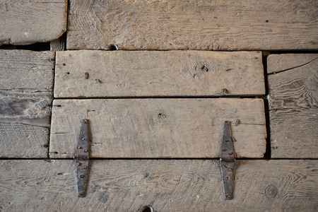 Worn wood trap door on the floor of the loft of a barn