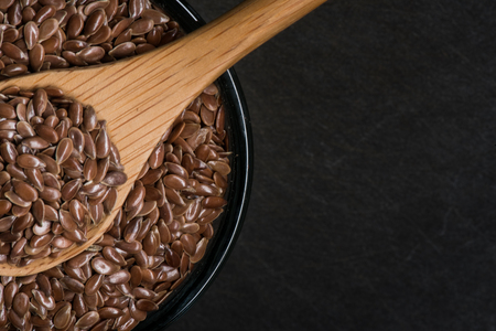 brown flax: Wooden spoon in bowl of brown flax seeds with slate cutting board in background