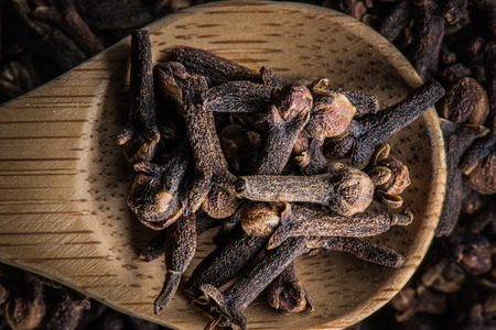 mulled wine spice: Wooden spoon with cloves in a pile of cloves Stock Photo