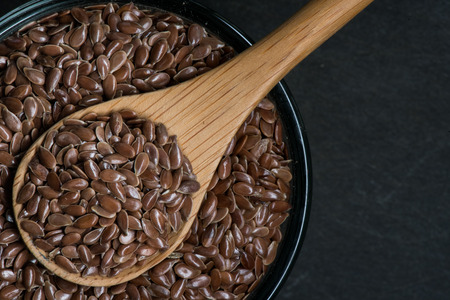 brown flax: Brown Flax Seed in Bowl with Wooden Spoon and Small Copy Space to right