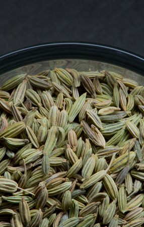 fennel seeds: Close Up Bowl of Fennel Seeds Edge against slate background Stock Photo