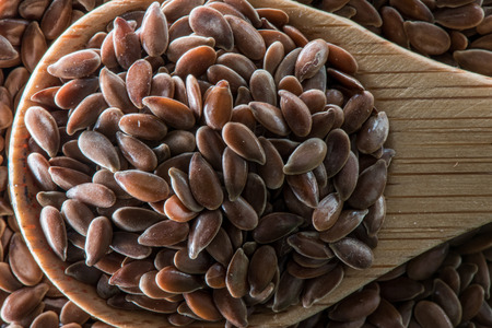 brown flax: Wooden Spoon Full of Brown Flax Seeds on top of flax seeds