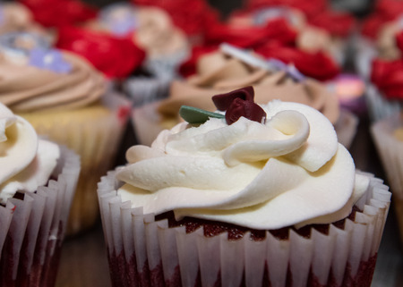 red velvet cupcake: Close up of Red velvet cupcake with a variety of cupcakes in the background
