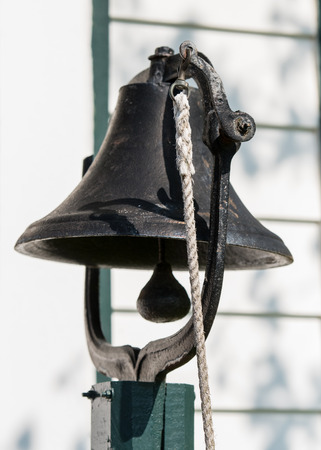 to beckon: Dinner Bell hangs on green post with white rope