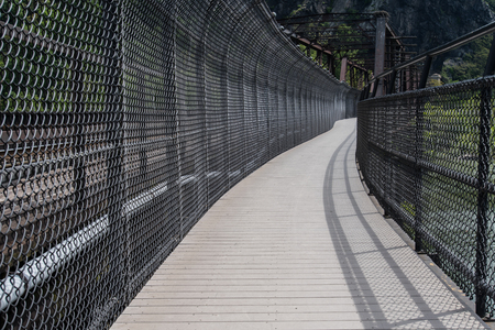 overly: Overly Protected Walkway next to railroad bridge Stock Photo