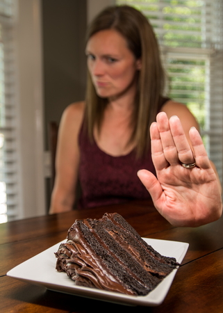 Woman Turning Down Chocolate Cake with hand held out
