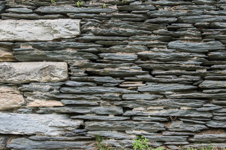 Thin Stone Stacked Wall with big stones on left Stock Photo