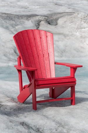 juxtaposition: Empty Red Chair Sitting on Glacier with a stream of snow melt behind