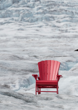 juxtaposition: Empty Red Chair with Glacier Ice Background and copy space Stock Photo