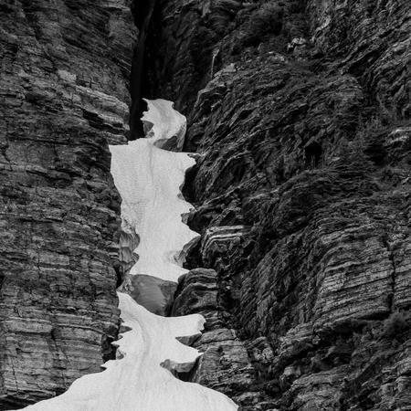 crevasse: Ice Suspended in Rocky Crevasse in black and white Stock Photo
