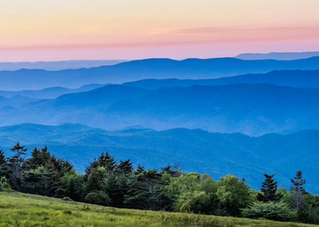 Hazy Blue Ridge Mountains at Sunset with grass bald in foreground Stock Photo