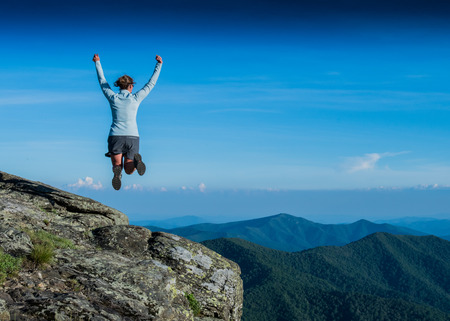 overlook: Leaping for Joy from a Rocky Overlook in summer Stock Photo