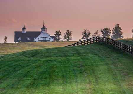 Black Fence Leads over the Hill in Kentucky horse country Stock Photo
