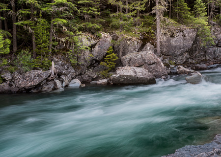 Water Rushes Past Boulders above McDonald Falls in Montana wilderness Stock Photo