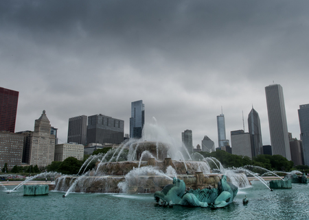 Chicago, United States: May 27, 2016: Buckingham fountain with skyline on cloudy day. After a long wait for restoration, the fountain is running during daytime hours.