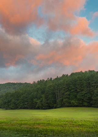 smokies: Coral Clouds Above Peaceful Green Field in Cataloochee Valley Stock Photo