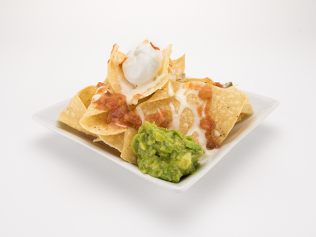 Nachos with queso, salsa, and guacamole isolated on white Stock Photo