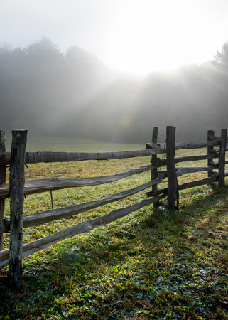 split rail: Low Angle View of Split Rail Fence and Foggy Sun Burst in early morning