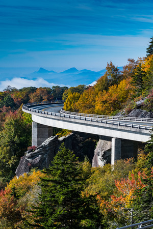 wispy: The Curve of Linn Cove Viaduct in Fall with wispy clouds in the valley
