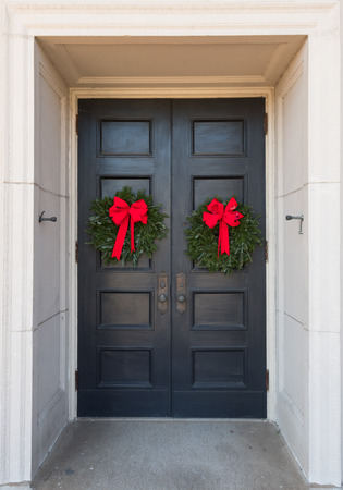 Two Christmas Wreaths on Building Doors with large red ribbons